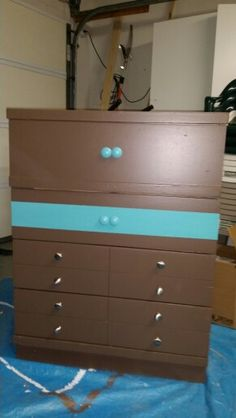 This one was in truly sad shape when it came to me. Removed peeling laminate. Sanded. Primed. Painted. New hardware. Now, it's happy again.  For a teen boy. Aqua color required to match his room. Decided the single stripe and knobs would give it interest and keep it masculine.   It's still and old dresser, but it isn't an eyesore any more.