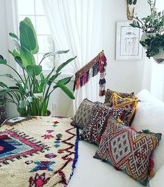 dreamy boho bedroom, Moroccan cushions and blanket, colourful tassel curtain tie-backs