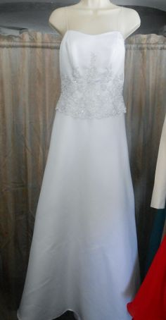This beautiful White gown with Silver Trim Wedding gown is preowned.  It is a size 4/6, Spaghetti straps and a Chapel detachable train.  Great for the reception.  No bustling.  Excellent condition. www.busymomsbridalshop.co