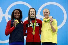 Gold medalist Simone Manuel of the United States, gold medalist Penny Oleksiak of Canada and bronze medalist Sarah Sjostrom of Sweden celebrate on the podium during the medal ceremony for the Women's 100m Freestyle Final on Day 6 of the Rio 2016 Olympic Games at the Olympic Aquatics Stadium on August 11, 2016 in Rio de Janeiro, Brazil.