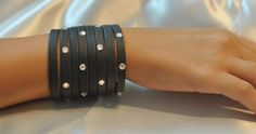 Nataly Noama Jewelled Black Leather Bracelet :  Simple yet fancy, this black African leather bracelet can be dressed up or down. The majority of the piece is divivded evenly into 8 strands that are adorned with 22 Swarovski crystal throughout. The strands gather into one piece of fine leather and the bracelet closes with a single snap button.