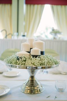 Centerpieces - stainless steel cake stands with 5 white pillar candles and a wreath of baby's breath