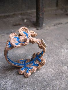 A nature inspired bracelet made out with electric blue and beige cotton with a beige button for closure. Great accessory, very subtle but at the same time