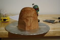 Boba Fett Cake:  Step 2 - cover in chocolate buttercream and carve out bottom sections of the helmet.