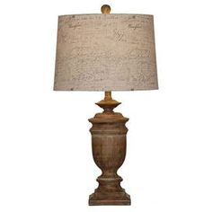 Carved wood table lamp with an aged bronze finish.  Product:  Table lamp   Construction Material: Wood  Color: Aged bronze Accommodates: (1) CFLS bulb - not included      Dimensions: 29 H x 16 Diameter