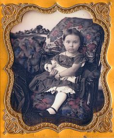 Antique photo of little girl and her doll, circa 1860's - 1880's.