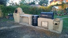 Cob kitchen, complete with pizza oven, ugly drum smoker, bbq and rocket stove.