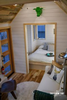 The Payette V2: a modern two bedroom tiny home with a stylish kitchen and a wood burning stove! Designed and built by TruForm Tiny Homes.