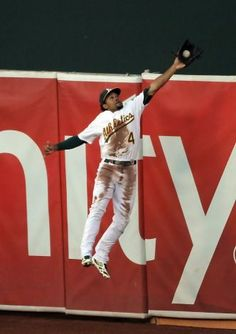 Coco Crisp quickly made up for his Sunday error by reaching over the center-field fence to catch Prince Fielder's second-inning drive. Photo: Carlos Avila Gonzalez, The Chronicle / SF
