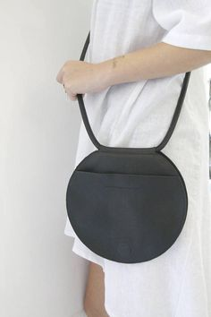 Handmade black leather crossbody purse with a unique shape and design. This circle purse is not only super unique, but its also versatile, lightweight and stylish. Can be carried as an everyday bag on your shoulder, as a cross body bag, a clutch, or around your waist. Each order over