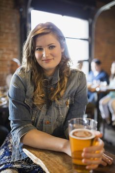 Portrait of smiling woman drinking beer in pub by Hero Images