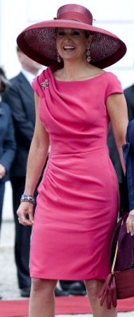Queen Máxima of the Netherlands wears a rose colored sleeveless summer dress paired with a spectacular burgundy picture hat with square crown and large mushroom shaped brim.  Visiting Poland, June 24, 2014