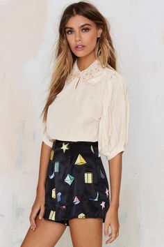 these layered black silk, embroidered geometric shapes and high-waisted silhouette are so cool