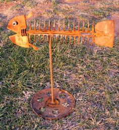 FISH SCULPTURE. MADE FROM DISCARDED GARDEN TOOLS LIKE HARD RAKES AND A HOE