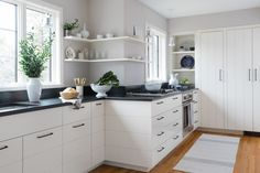 like this mix: country kitchen with painted cabinets, dark counters, wood floor, downdraft stove & wall oven, could do dark or silver colour hardware, add some closed uppers or widen shelves near sink, has panel cut like drawers over dishwasher