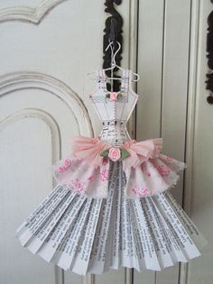 This adorable ballroom style dress miniature is made from music sheets, pages and crepe paper with an overskirt of soft pink floral fabric.  It is carefully stitched in pink cotton with pale pink ribbon roses trim glued in place.