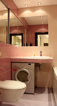 Washing mashine and mirrors in a small bathroom
