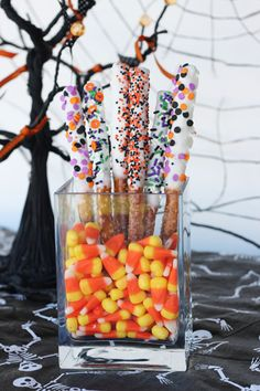 "Dipped Pretzel Rods are instantly transformed into ""Witches Wands"" with a little Halloween pizazz! Put them in containers with candy corns t..."