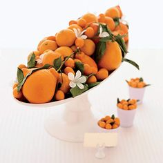 Tangerines, kumquats, and orange blossoms in white pedestal container. The tiny klmquat containers could be used for place cards.    Unique Wedding Centerpiece Ideas : Wedding Flowers Gallery