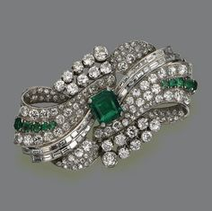 EMERALD AND DIAMOND BROOCH, CIRCA 1935 The plaque designed as a stylized bow-knot, set in the center with an emerald-cut emerald weighing approximately 4.75 carats, completed by 122 old European-cut and single-cut diamonds and 38 baguettes weighing approximately 16.75 carats, the ends decorated with 10 cushion-shaped oval and emerald-cut emeralds, mounted in platinum.