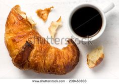 fresh croissant and a cup of black coffee, isolated on a white cutting board - stock photo