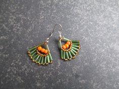 Leuke oorbellen in de vorm van een waaier met de kleuren groen, bruin en oranje kralen als opvallend detail.