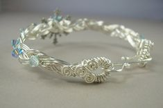 This braided wire bracelet features an antique silver snowflake as a centerpiece, glittering with Swarovski crystals in the icy pale blue colors of winter. The crystals continue around the braided band of the bracelet, and the large loops at the ends of the bracelet are completely