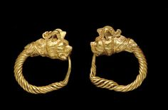 A PAIR OF GREEK GOLD LION-GRIFFIN EARRINGS   HELLENISTIC PERIOD, CIRCA 3RD CENTURY B.C.   Each formed from a hoop of spirally-twisted wire tapering to a single wire point, the head of a horned lion-griffin emerging from a collar ornamented with filigree tongues, plain wires and filigree spirals, the horns and crest made separately and inserted into the feline head, formed of two halves, with fine detail for the mane and whiskers, the open mouth to receive the tip of the hoop