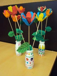 Flors amb gerro Material: oueres, actimel, palets de fusta, cartolina, tisores, colors, gomets, pintura.