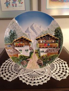 """George Schmider - Zeller Ceramics, collectors plate. This textural, 3D plate is large, with a 12"""" diameter. A beautiful scene street scene augmented with the Alps in the background."""