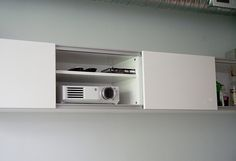 Install shelving into wall to store projector and when not in use can hide away