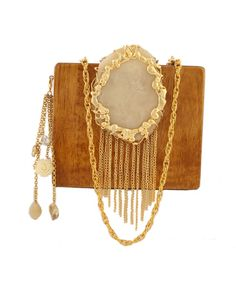 Mustard And Ivory Wood And Resin Waterfall Clutch   Create a dazzling stylish look by accessorizing with this glamorous clutch from us. The mustard wood square plain clutch added with an oval-round ivory resin piece on the top has been well edged golden carved design with golden danglers. The group of golden flowers on the top for closure gives a true sparkling gleam to the accessory. Make it more trendy with the extra chained danglers given to attach them on the side of the clutch.