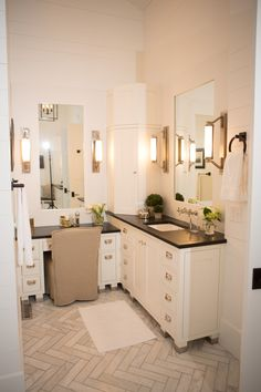 white bathroom with white wall, cabinetery, black soapstone top, tile flooring, mirror, sconces of Longer Vanity with L Shaped Vanity in the Bathroom