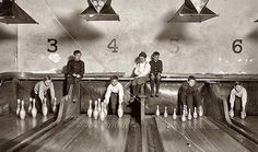 """Pin boys"" set up bowling pins while people play games (1914)."