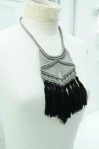 A unique macramé necklace from my winter collection 2011 with black cord (4mm)   and ten sand-color tassels at the end.There is a gold vintage button for closer .