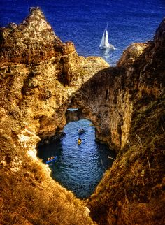 """Lagos, Portugal. We walked out to what was historically known as """"the end of the world"""" and saw a thunderous storm brewing over the sa. Some of the most remarkable landforms anywhere."""