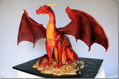 This amazing Smaug cake was made by the Cakerator. It took 4 days to make a cake of this amazing detail. The dragon was composed of lemon cake, white chocolate ganache, modeling chocolate, and fondant; all on top of an elaborate internal structure. The wings were made from copper tubes welded together and then covered in modeling chocolate. The membrane of the wings were a mixture of fondant, modeling chocolate, and gum paste. The excellent color variations of Smaug were obtained by using…