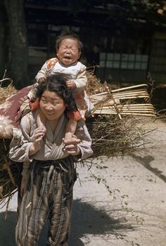 Japan 1940s. A smiling mother carries a crying baby and a large bundle of sticks
