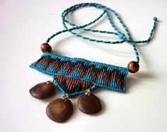 Intricate teal/light blue, green and brown coloured necklace made in macrame with three ceiba seeds collected by ourselves dangling from it. Apart