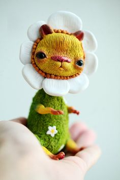 The flower is handmade of sculpey living doll and fur fabric, painted with acrylics and sealed with matte finish. His eyes are glass.    Please keep in
