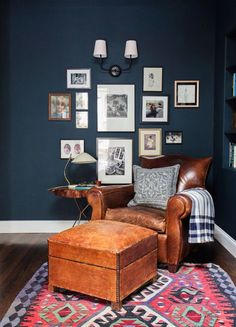 Vintage leather chair in bourbon with navy walls and gallery wall.