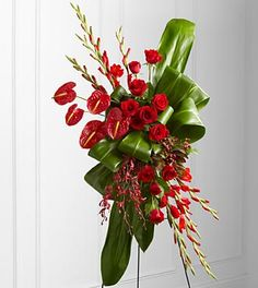 Sympathy Flowers - FTD Sweet Thought Standing Spray - The FTD Sweet Thought Standing Spray is an expression of sophistication and beauty to commemorate the life of the deceased at their final memorial service. Brilliant red roses, gladiolus, anthurium, James Storei orchids and hypericum berries create an exquisite arrangement offset by bright green ti and aspidistra leaves folded in a unique pattern to create a presentation symbolizing the unending love you have for the departed. Displayed…