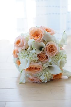Peach roses, calla lillies and white hydrangea bridal bouquet