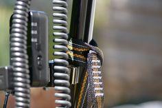 Auch an oder mit einer Manfrotto Nano Clamp (386B) geht Zubehör wie hier ein Akkupack ans Stativ. Eine kleine Bandschlinge (hier Elliot für EUR 2,99) ist da hilfreich.
