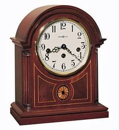 """Howard Miller Mahogany finished Barrister  mantle clock features inlays of mahogany and an intricate oval of variegated maples.  This clock has a warm white face with black numerals and hands, and a brass finished bezel. The fluted columns with wooden column caps grace each side. This clock has a Key-wound, Westminster chime movement with durable bronze bushings and silence option.  Size: Height: 11-3/4"""" Width: 9-1/2"""" Depth: 5-1/4"""""""