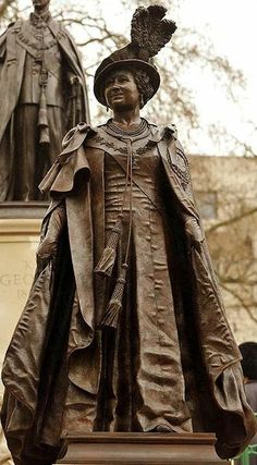 Bronze Statue of Queen Elizabeth (Queen Mother) on The Mall, London, overlooked by the statue of her husband King George VI.