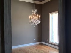 Dining area with pine floors and chandelier.