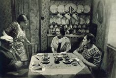 Mrs. Barber lives in Lollard Street, off Lambeth Walk. Left is Mrs. Barber's 88-year-old father, who sells straw-bags in Lambeth Walk on Fridays and Saturdays, if fine. Right is her daughter. A cup of cocoa is their morning custom. Source: Picture Post. December 31, 1938