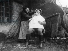A female barber giving a man a shave, 1915 (b/w photo) / SZ Photo