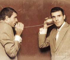 Vintage Photograph Of Two Business People Exchanging Information Down The Line Of A Tin Can Telephone In A Retro Communication Conceptual by Ryan Jorgensen